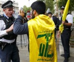 LONDON, UNITED KINGDOM - SEPTEMBER 09: Police officers talk to an anti-Israel demonstrator who is wearing a Hezbollah flag during the pro and anti-Israeli demonstrations outside Downing Street in London, England ahead of a visit by Israeli Prime Minister Benjamin Netanyahu on September 9, 2015. (Photo by Tolga Akmen/Anadolu Agency/Getty Images)